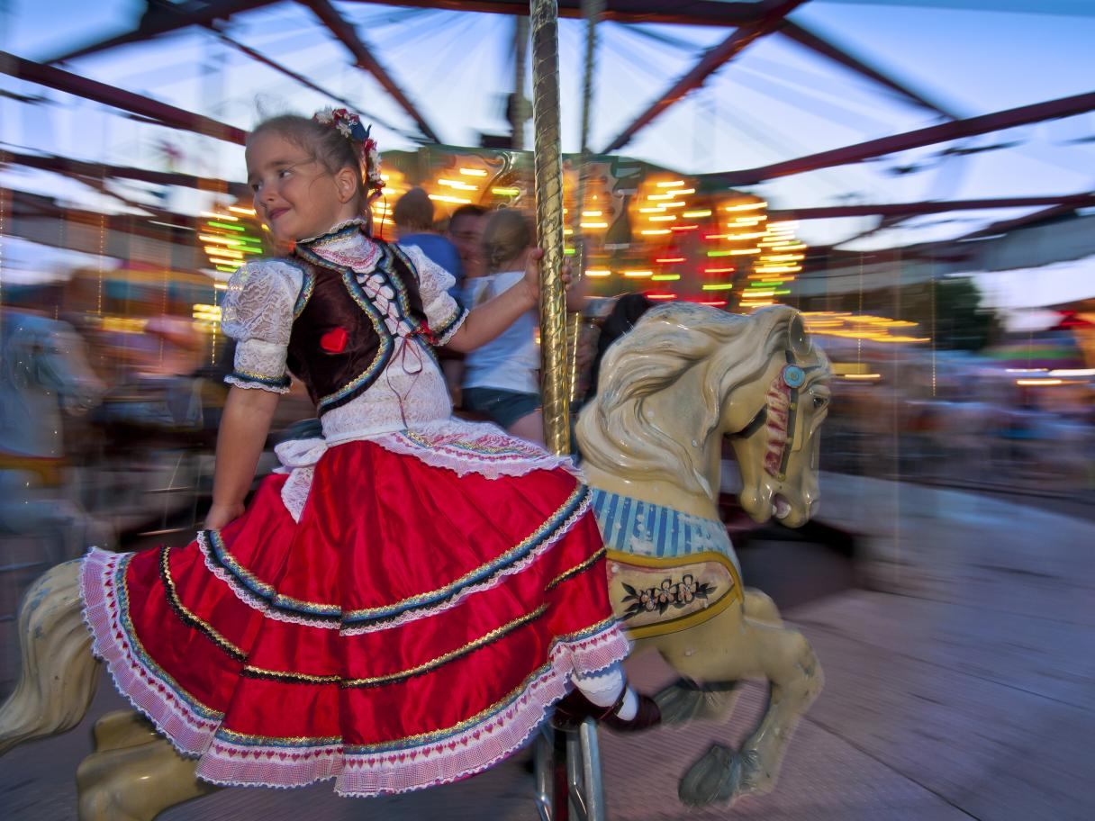 Girl riding a carousel at Czech Days