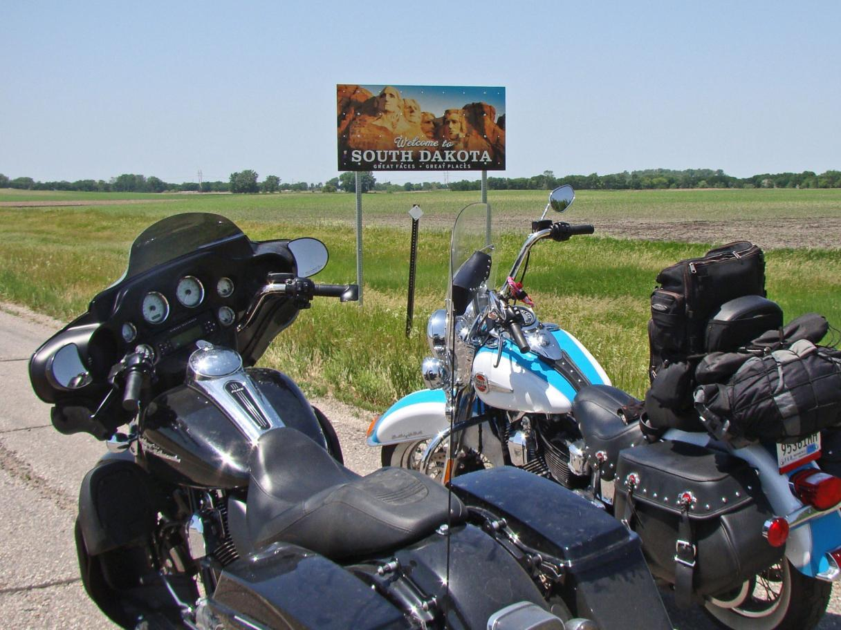 Motorcycles in front of the South Dakota state sign