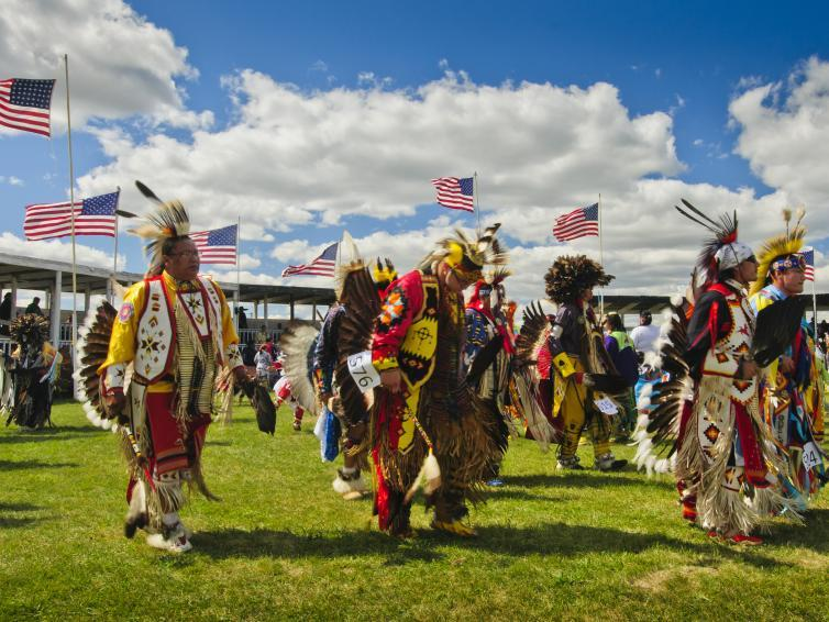 Native Americans dress in feathers and beads at a powwow