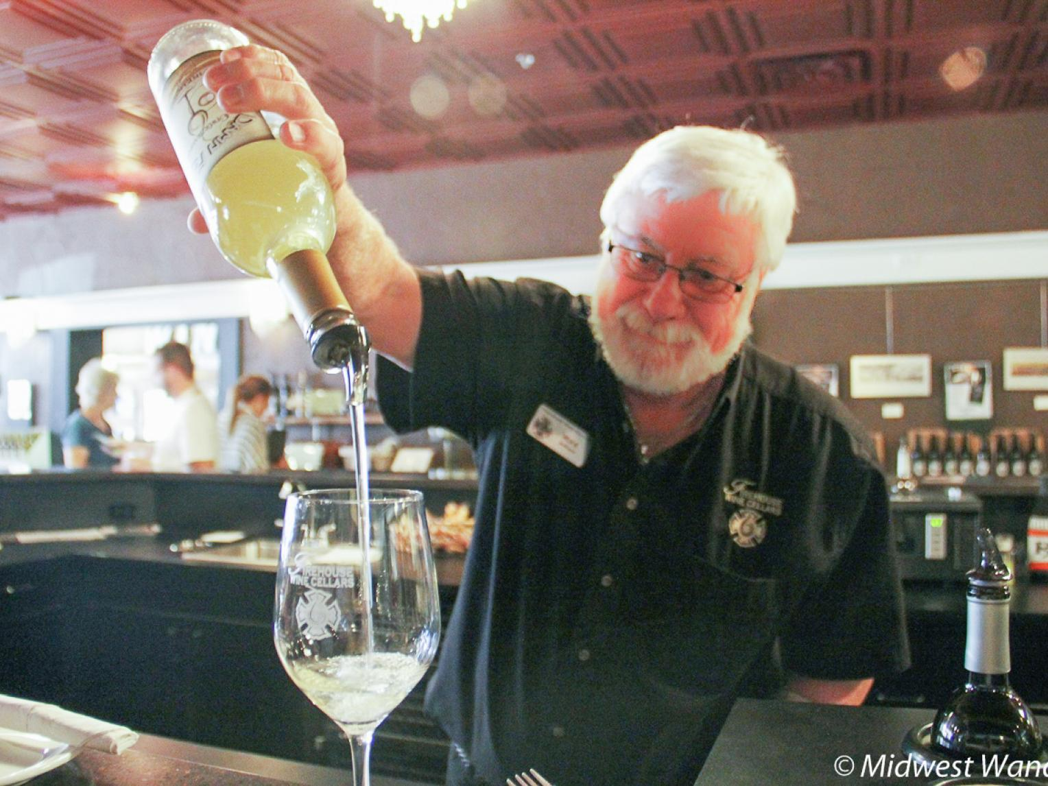 A staff member at Firehouse Wine Cellars pours a glass of wine.