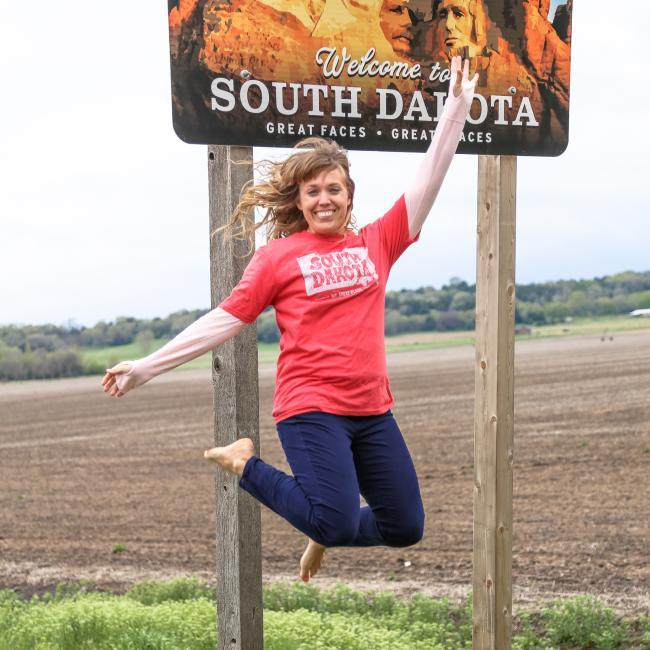 Jumping in front of the Welcome to South Dakota sign
